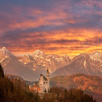 Пейзаж с известным замком нойшванштайн, горы на заднем плане и величественное небо, германия