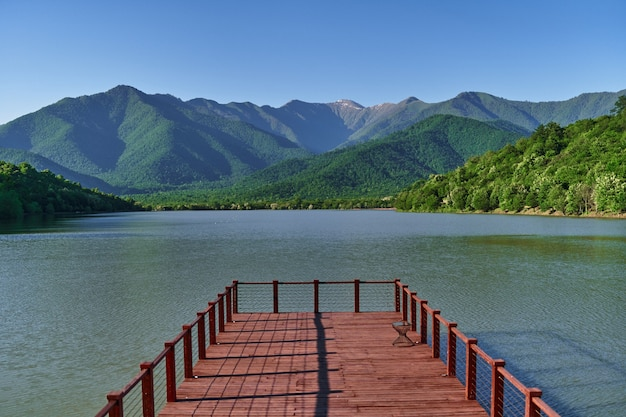 Landscape of wooden pier with beautiful lake and mountains view. serene quiet peaceful atmosphere in nature