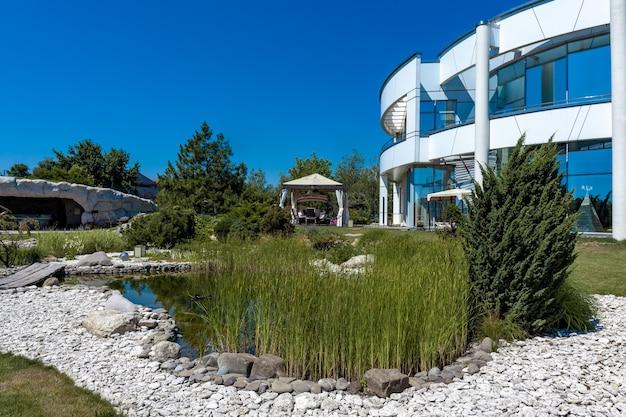 Благоустроенный задний двор загородной виллы с патио и естественным прудом летом