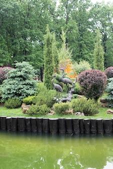 공원의 조경, 다양한 식물, 호수 및 황새 동상