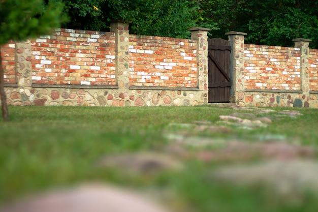 Ландшафтный дизайн. забор из красного кирпича с коричневыми деревянными воротами во дворе частного дома. каменный путь.