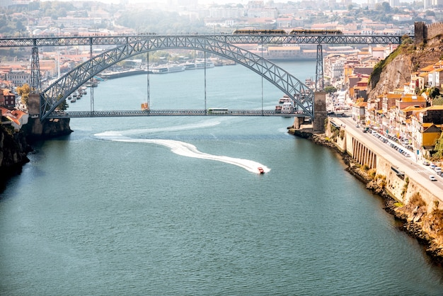 Ландшафтный вид на реку дору с поплавками на катере и красивый железный мост в городе порту, португалия