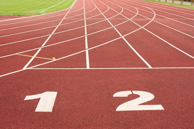 Lanes of a red race track with numbers in the stadium.
