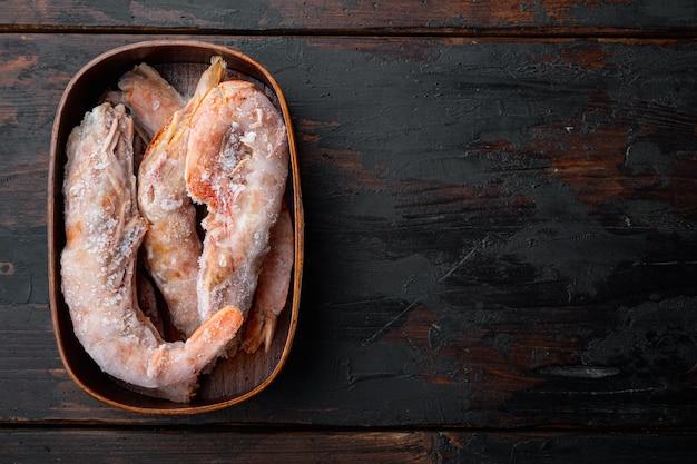Langoustines 아르헨티나 냉동 세트, 나무 상자, 오래 된 어두운 나무 테이블, 평면도 평면 누워