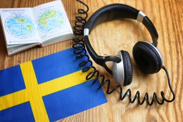 Наушники языкового курса и флаг на деревянном столе