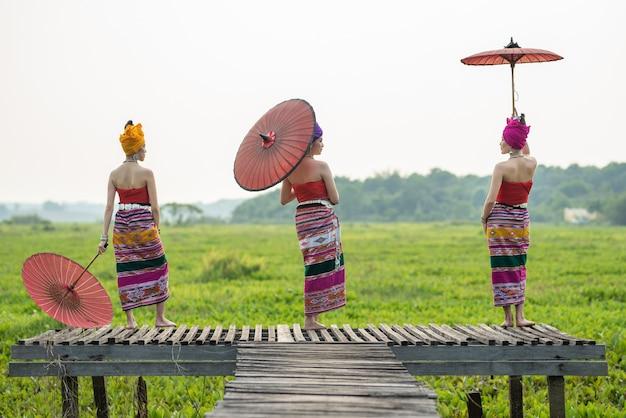 Азиатская тайская женщина lanna 3 в традиционном поступке зонтика бумаги владением руки платья любит модель на деревянном бамбуковом мосте с небом overcast.