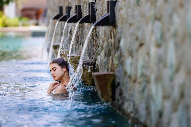 スイミングプールとビーチの近くの熱帯lansdcapeの豪華なビーチフロントのホテルリゾートで休暇を楽しんでいる女性