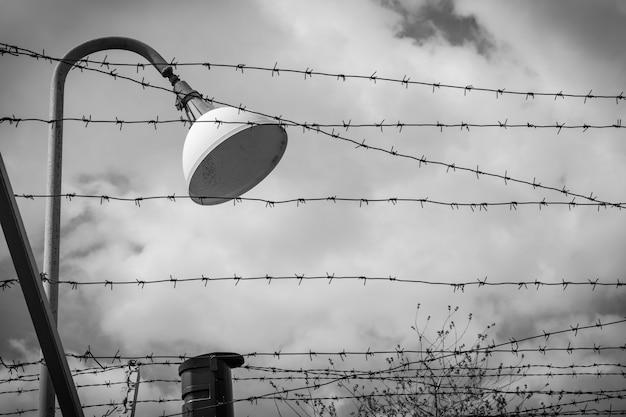 전기가 연결된 랜턴과 철조망 - 흑백 사진.