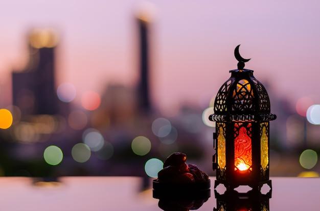 ラマダンカリームの夜明けの空と街のボケ味の明るい背景のランタンとナツメヤシの果実。