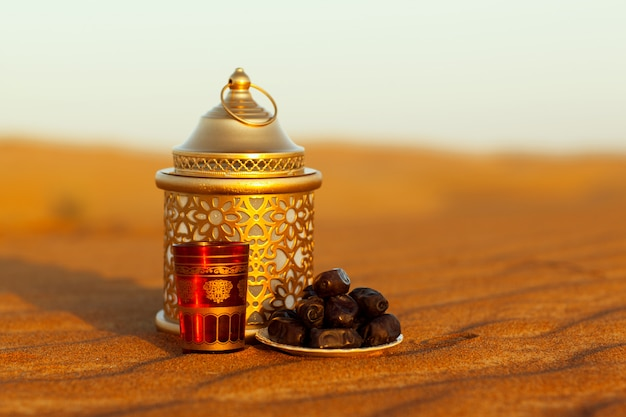 Lantern, cup and dates are on the sand in the desert