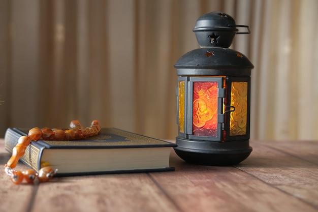 Фонарь свет священной книги коран и четки на столе крупным планом