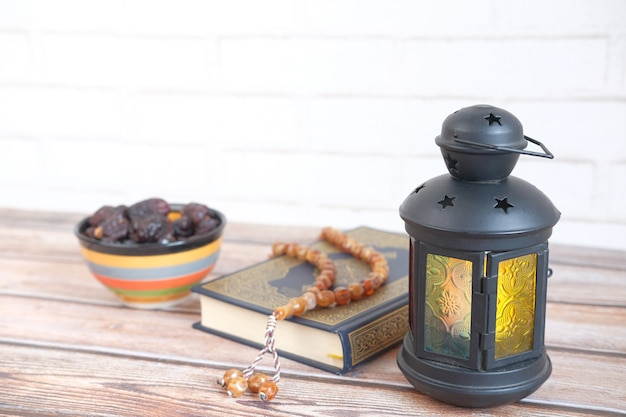 Lantern light holy book quran and rosary on table close up