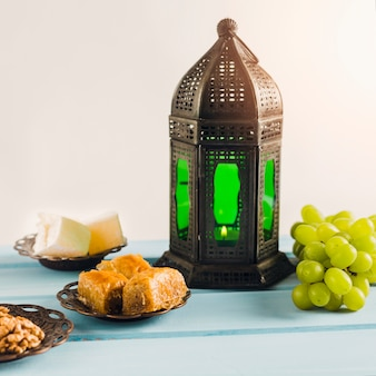 Lantern near green grape with baklava and turkish delights on saucers