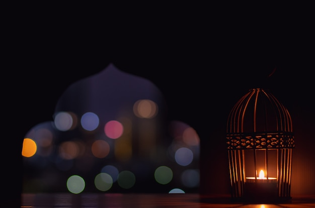 Lantern put in front of paper cut in mosque shape.