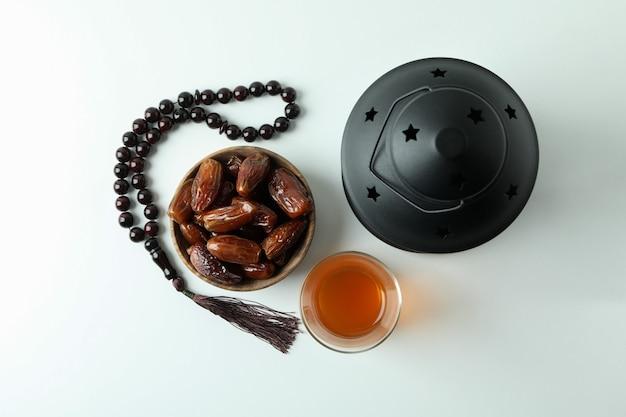 Фонарь, четки, стакан чая и миска фиников на белой поверхности