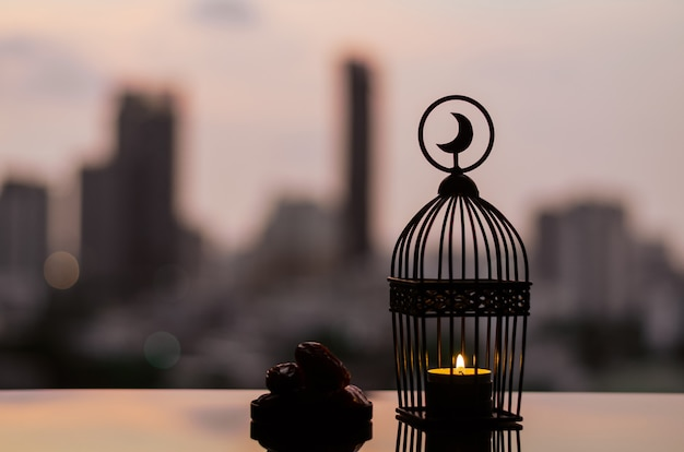 Lantern and small plate of dates fruit with city background for ramadan kareem.
