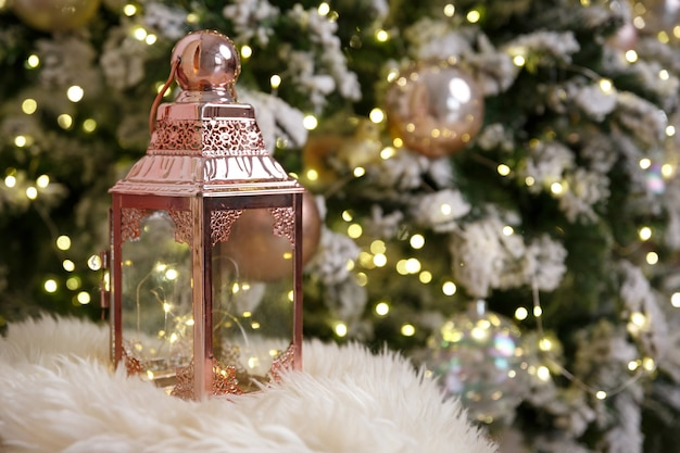 Lantern stands on fur plaid, against background of bokeh lights of christmas tree garland
