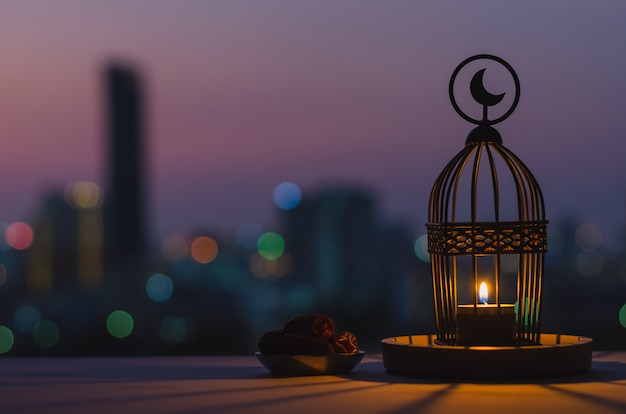 ラマダンカリームの聖なる月のイスラム教の饗宴のための夕暮れの空と街のボケ味の明るい背景の日付フルーツの上部と小さなプレートに月のシンボルがあるランタン。