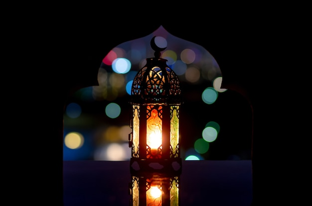 Фонарь с символом луны на вершине с городским светом боке и размытым фокусом фона мечети