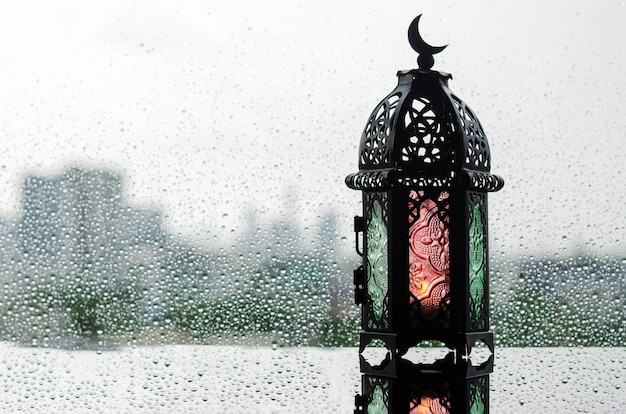 Lantern that have moon symbol on top put on window with rain drop for islamic new year