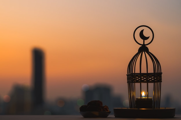Lantern that have moon symbol on top and small plate of dates fruit with dusk sky and city background for the muslim feast of the holy month of ramadan kareem.