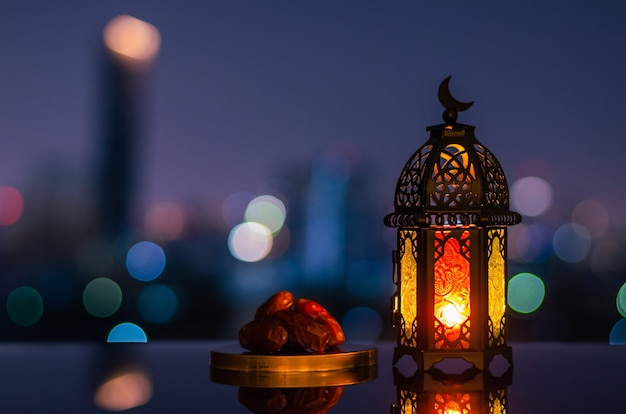 Lantern that have moon symbol on top and small plate of dates fruit with night sky for ramadan kareem.