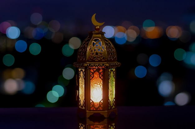 Lantern that have moon symbol on top with night sky and city bokeh light background.