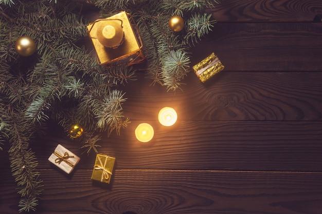 木製のテーブルにキャンドルとクリスマスツリーの枝とランタン。上から見る