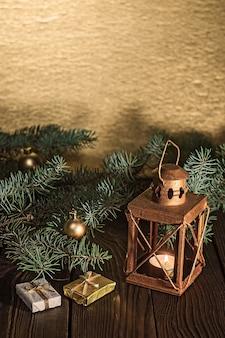 木製のテーブルにキャンドルとクリスマスツリーの枝とランタン
