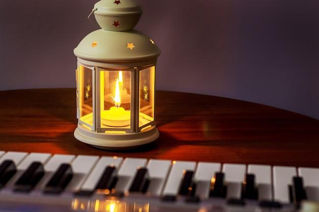 저녁에 피아노 근처에 촛불이있는 랜턴