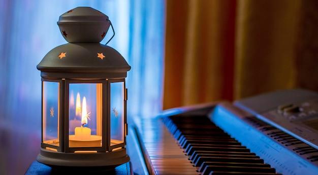 저녁에 창문을 향해 방의 피아노 옆에 촛불이 달린 랜턴