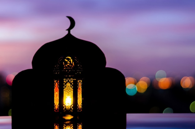 Lantern with blurred focus of mosque background that have moon symbol on top and dawn sky