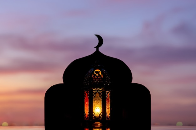 Lantern with blurred focus of mosque that have moon symbol on top and dawn sky.