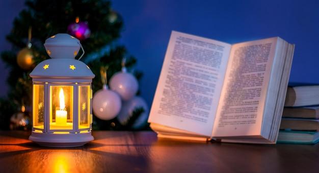 クリスマスツリーの近くに本と開いた本とランタン。キャンドルライトで読む_