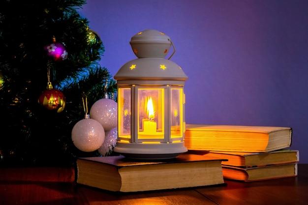 クリスマスツリーの近くにキャンドルと本のあるランタン_