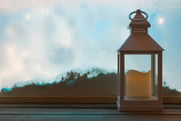 Lantern with candle on wood board near bank of snow through window