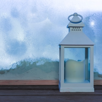 Lantern with candle on wood table near bank of snow through window