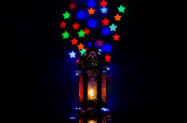 イスラムの新年とラマダンカリームのコンセプトのためのカラフルな星型のボケライトが付いたランタン。