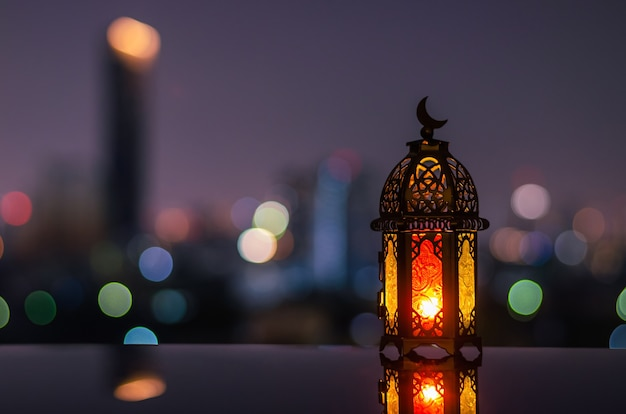 Lantern with dusk sky and city bokeh light background for ramadan kareem.