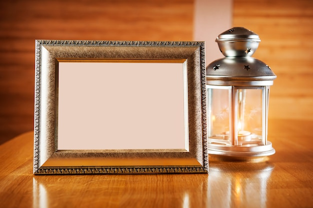 Lantern with frame on wooden table