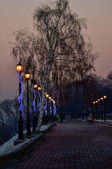На набережной на закате горят фонари