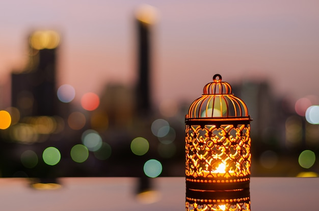 Lanterns with dawn sky and city bokeh light background for ramadan kareem.