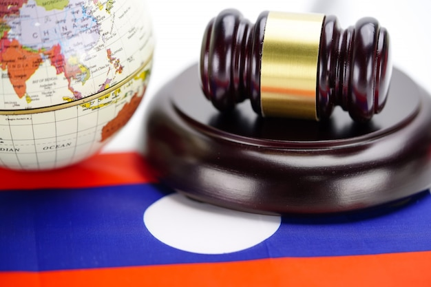 Laos flag and judge hammer with globe world map. law and justice court concept.