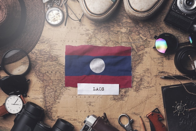 Laos flag between traveler's accessories on old vintage map. overhead shot