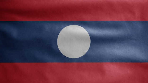 Laotian flag waving in the wind. close up of laos banner blowing, soft and smooth silk. cloth fabric texture ensign background.