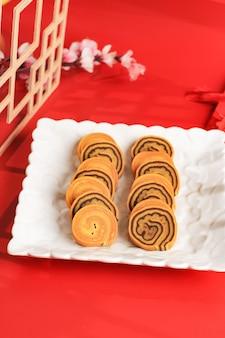 Ляпис законный ролл торт или индонезийский тысячный слоеный пирог в белой тарелке на красном фоне. этот торт подается на празднование китайского нового года (имлек)