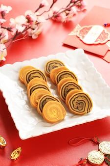 Ляпис законный ролл торт или индонезийский тысячный слоеный пирог в белой тарелке на красном фоне. этот торт подают на празднование китайского нового года (имлек)