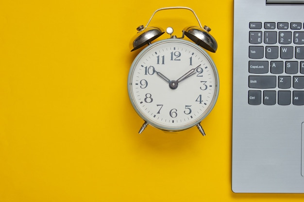Laptop and alarm clock on yellow paper