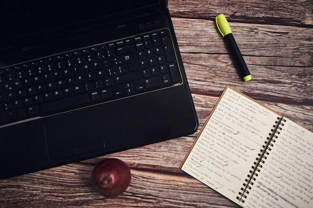 Ноутбук и блокнот на деревянном столе