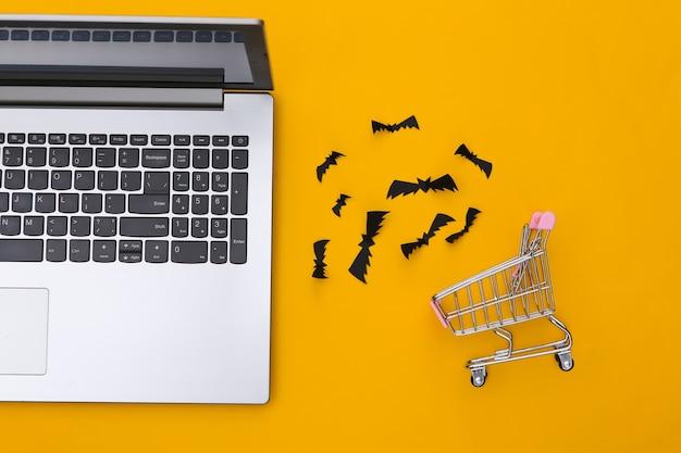 노란색 배경에 종이 컷 박쥐가 있는 노트북 및 쇼핑 트롤리. 할로윈 테마입니다. 평면도